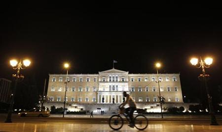 A man rides his bicycle past the parliament building in Athens