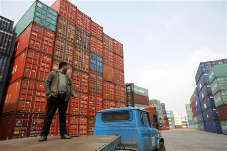 A worker stands on a truck as he waits to transport shipping containers at the Port of Shanghai