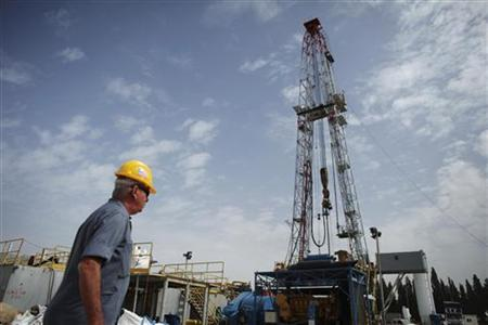 A worker walks near an oil rig in Karkur, northern Israel October 17, 2010.