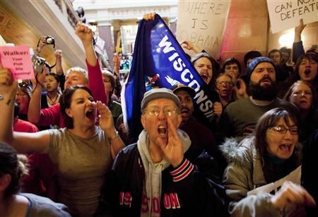 Protestors yell outside of the office of Wisconsin State Governor Scott Walker after the signing of the ceremonial bill, after the Republican-controlled House and Senate eliminated almost all collective bargaining for most public workers, at the state Capitol in Madison, Wisconsin March 11, 2011. REUTERS/Darren Hauck