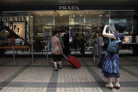 Mainland Chinese visitors take a picture outside a Prada store in Hong Kong