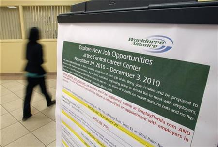 A job seeker walks past a sign at the Workforce Alliance Career Center in West Palm Beach