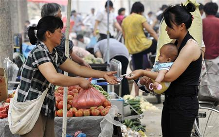 A woman holding her child buys tomatoes at a market in Heze city