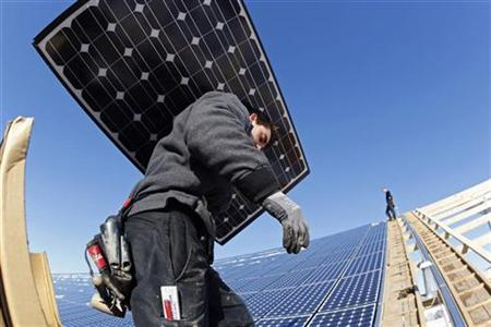 Workers install solar panels at a farm