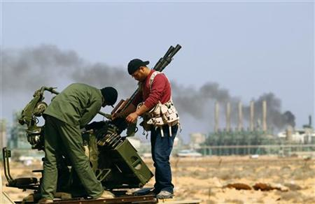 Rebel fighters fix their mounted anti-aircraft gun near the oil refinery at Ras Lanuf in Libya