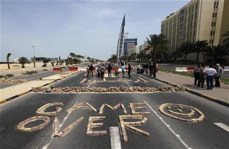 "Anti-government protesters form the words ""Game Over"" with bricks as they block the roads from riot police at the junction of Bahrain Financ"