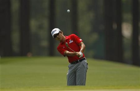 Kim Kyung-tae of South Korea hits his approach shot to the eighth green during third round play in 2011 Masters golf tournament in Augusta