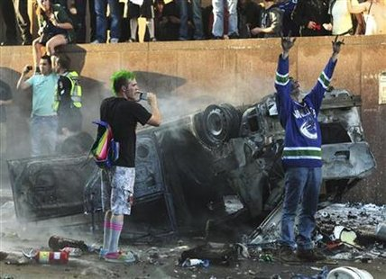 Canucks fans scream and take photos of an overturned burnt pickup truck during riots in downtown Vancouver after the Canucks lost the NHL St