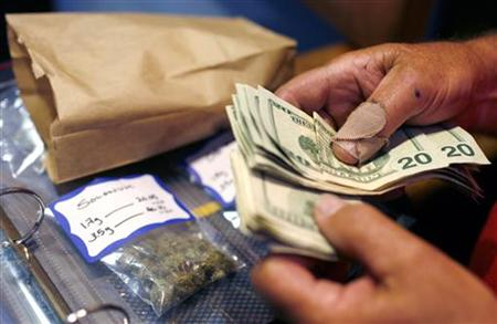 A customer makes a medical marijuana purchase at the Coffeeshop Blue Sky dispensary in Oakland, California June 30, 2010. REUTERS/Robert Gal