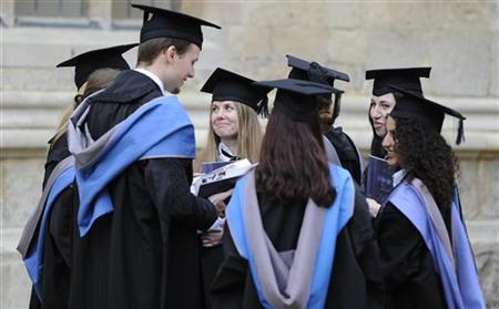 A group of graduates gather outside the Sheldonian Theatre after a graduation ceremony at Oxford University, England