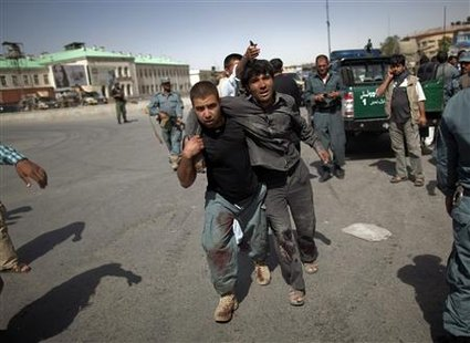 Afghan policeman helps a wounded man away from the site of an attack at a Kabul police station