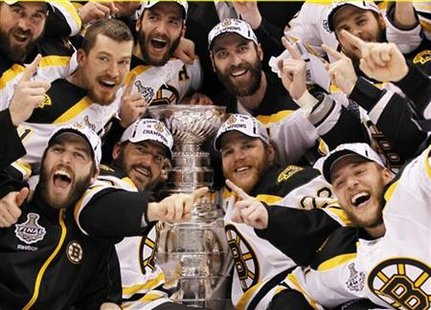 Bruins players celebrate with the Stanley Cup after they defeated the Canucks to win the NHL championship in Game 7 of the finals in Vancouv