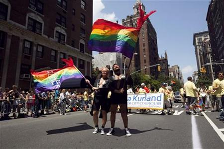 Men dressed in tuxedo jackets wave flags in the annual Gay Pride Parade in New York