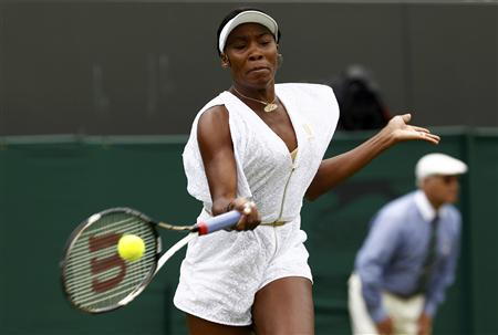 Venus Williams of the U.S. hits a return to Akgul Amanmuradova of Uzbekistan at the Wimbledon tennis championships in London