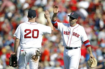 Boston Red Sox first baseman Adrian Gonzalez celebrates with teammate third baseman Kevin Youkilis after defeating the Milwaukee Brewers in