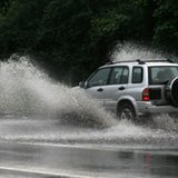 An SUV runs through a flooded road