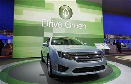 "The 2010 Ford Fusion is seen in front of a sign that reads ""Drive Green"" at the 2010 North American International Auto Show during press day"