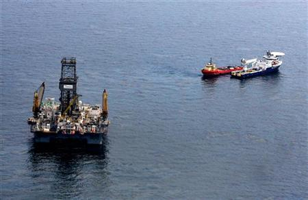 Oil floats on the surface of the Gulf of Mexico around the Transocean Development Driller III, which is drilling a relief well, at the site