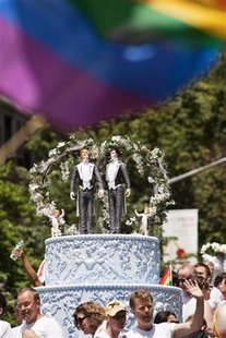 Two grooms are placed atop a wedding cake to protest in favor of gay marriage in the annual Gay Pride Parade in New York