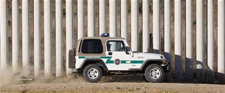 Border Patrol agent drags border road next to tiers of fences along US-Mexico border in San Diego