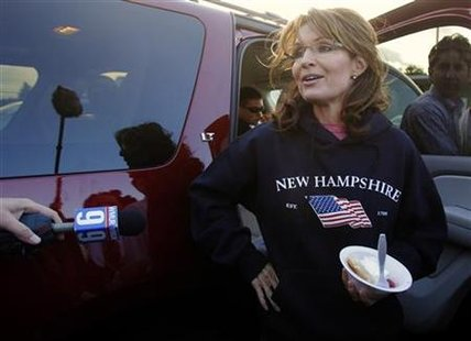 Former Alaska Governor Sarah Palin, wearing a New Hampshire sweatshirt, talks to reporters following a stop at a clam bake at a private resi