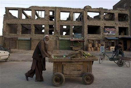 An elderly man pushes a cucumber cart on a street in Kabul