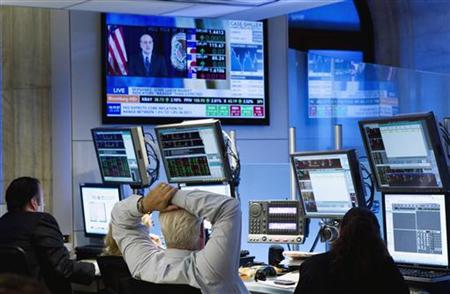 Traders listen to chairman of the Federal Reserve, Ben Bernanke, make an address on a television screen as they work on the floor of the New
