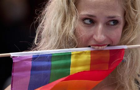 A protester clenches a rainbow flag with her teeth at a demonstration outside Sheraton Hotel where President Obama was attending a function