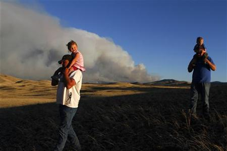 Men carrying children look at the smoke from the Wallow wildfire in Apache County, Arizona
