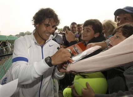 Rafael Nadal of Spain signs autographs as he leaves a practise court at the Wimbledon tennis championships in London