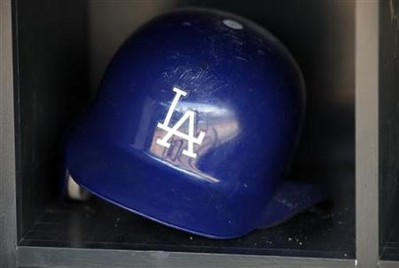 A batting helmet reflects the dugout of the Los Angeles Dodgers before game against Twins