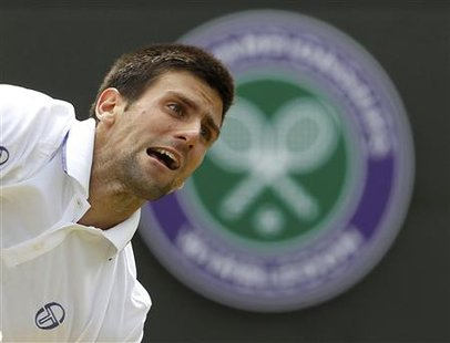 Novak Djokovic of Serbia serves to Bernard Tomic of Australia during their quarter-final match at the Wimbledon tennis championships in Lond