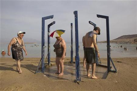 Tourists take a shower after bathing in the Dead Sea resort of Ein Bokeq