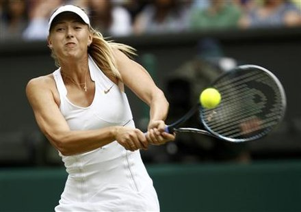 Maria Sharapova of Russia hits a return to Sabine Lisicki of Germany during their semi-final match at the Wimbledon tennis championships in