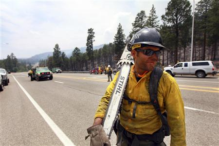 A fire crew member is seen as fire crews are deployed in order to attack hotspots from the Las Conchas wildfire near Los Alamos, New Mexico