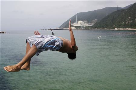 A man on vacation backflips as he dives into the sea in Tsuruga, Fukui prefecture