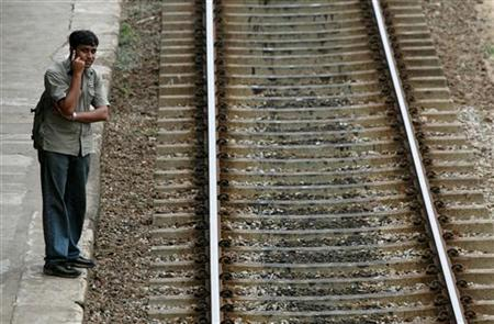 A man waits for a commuter train in Colombo