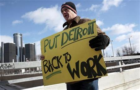 Unemployed worker Pollock carries a sign outside Cobo Center to demonstrate for jobs and good wages before start of press days at North Amer