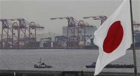 A Japanese national flag is seen in front of cargo cranes at an industrial port in Tokyo