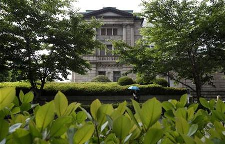A woman walks past the Bank of Japan building in Tokyo