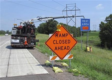 "Workers erect a ""closed"" sign over a highway rest stop sign near Hinckley"
