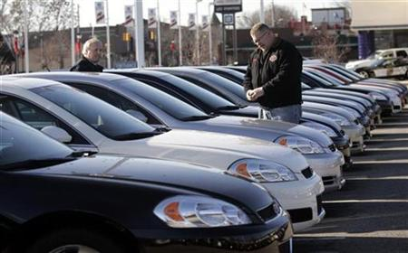 Car salesman Ray Schaffer shows a customer a 2009 Chevrolet Impala sedan at a dealership in Dearborn, Michigan