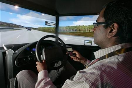 A man texts on his mobile phone while driving in a simulator during the 2010 International CES in Las Vegas