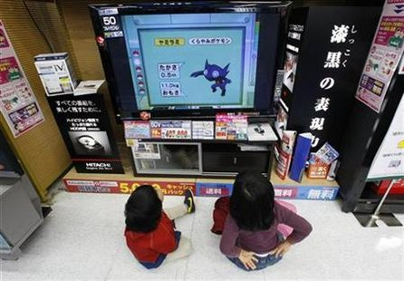 Children sit on the floor as they watch Hitachi's television at an electronics shop in Tokyo