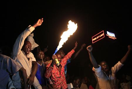 People take part in South Sudan's independence day celebrations near the countdown clock in Juba