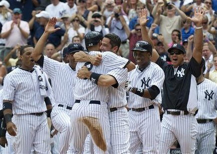 New York Yankees Jorge Posada hugs Derek Jeter after Jeter hit a solo home run and his 3000th career hit against the Tampa Bay Rays in New Y