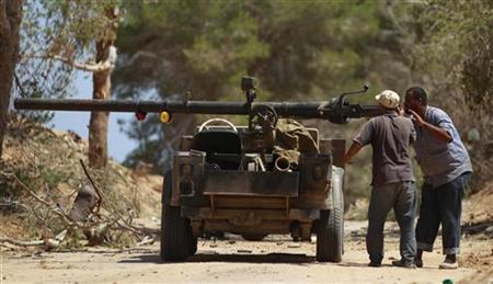 Rebel fighters load their vehicle-mounted weapon on the outskirts of Zlitan, near Misrata's western frontline