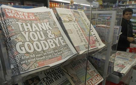 Copies of the final edition of the News of the World, alongside other Sunday papers, are displayed for sale in a newsagent in London