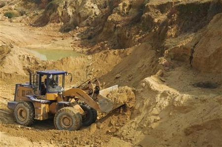 A worker drives a skip loader while working at the site of a rare earth metals mine at Nancheng county
