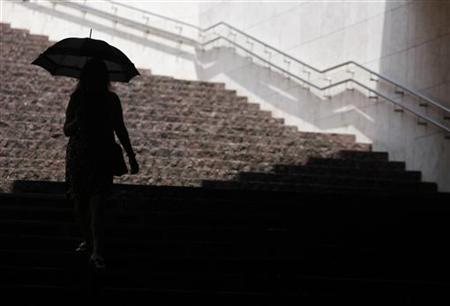 A woman using an umbrella to shield herself from the sun as she walks down stairs at a business complex in Tokyo